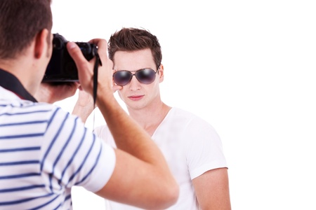 professional male photographer taking a picture of his male model on white background photo