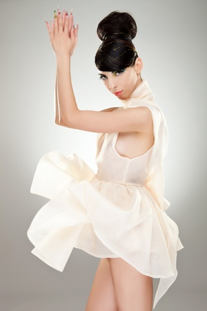 white dress: side view of a sexy young woman playing with her dress on studio background Stock Photo