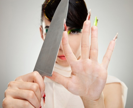fashion woman with nice manicure, sharpening her big nails with kitchen knife photo