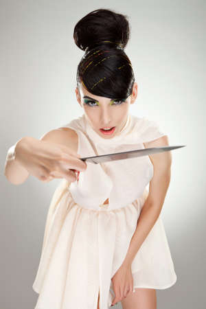 sexy woman in dress attacking with big kitchen knife on studio background photo