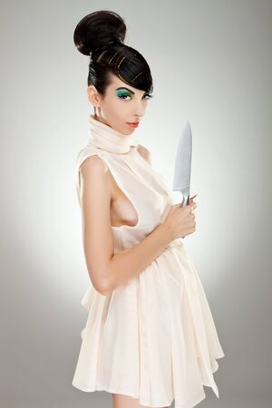 sexy young woman in a dress holding a big knife in her hand photo