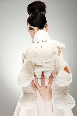 Brunette girl in dress giving you a teddy bear  photo