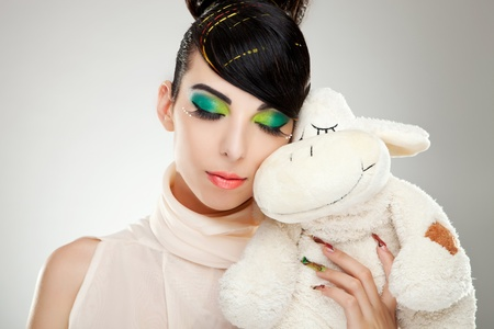 Fashion girl posing with teddy against her face on studio background photo