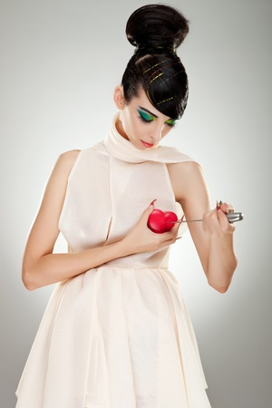 brokenhearted woman in fashion dress pointing a big kitchen knife at her heart photo