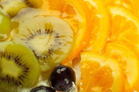 cloesup: cloesup of a fruity tart with kiwi, grapes and orange topping