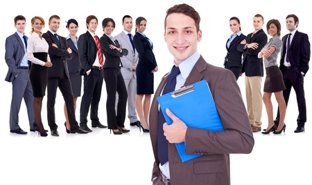 Leader holding a clipboard with business team behind, isolated on white  young business man holding a clipboard in front of a large happy business team photo