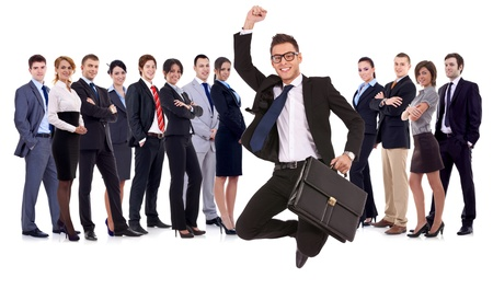 business man holding briefcase jumping with his business team formed of young businessmen and businesswomen standing over a white background with reflections  photo
