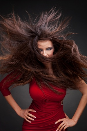 blow up: Young woman with hair flying  on dark background