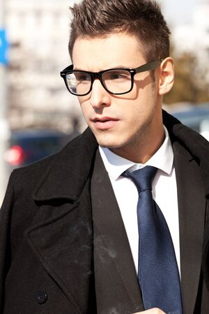 young businessman wearing glasses and looking to a side , outdoor picture Stock Photo - 13311965