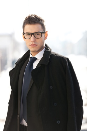 man with glasses: Businessman wearing suit , coat and glasses, looking to the camera - outdoor picture Stock Photo