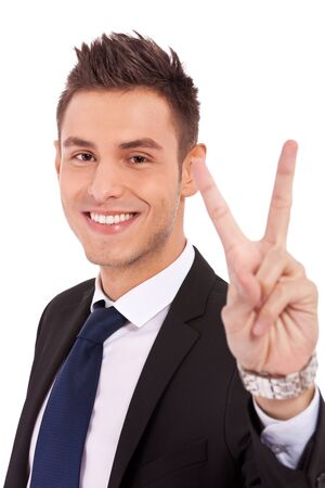 Attractive man in a suit shows a sign of peace or victory on white background photo