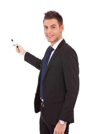 presenting: handsome young business man in a suit pointing with a pen on white background