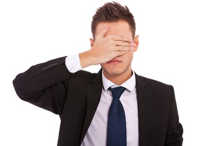 no idea: business man making the see no evil gesture over white . young businessman covering his eyes with his hand  Stock Photo