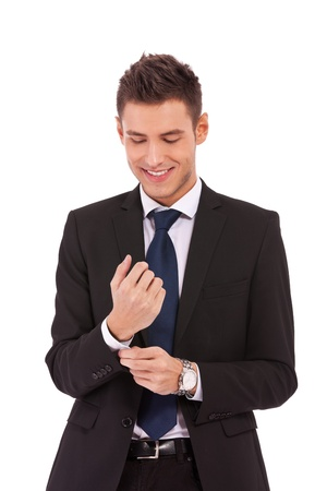 getting ready: young smiling business man buttoning his sleeve and getting ready to work