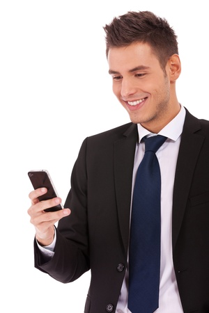 Handsome happy business man reading an SMS on smartphone against white background photo