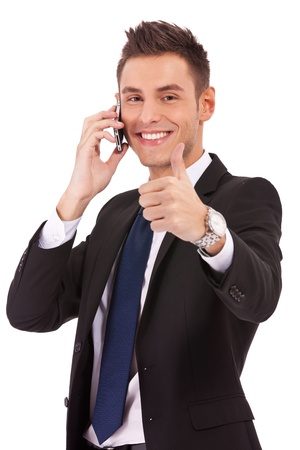 hand holding phone: smiling young business man talking on the phone and making ok gesture. Isolated on white background  Stock Photo