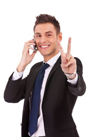 victory sign: picture of a business man making victory sign while talking on the phone