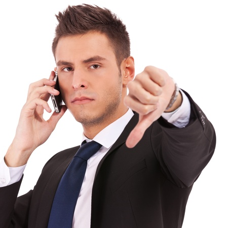 disapproving: Business man with bad news on his cell phone disapproving . negative answer  Stock Photo