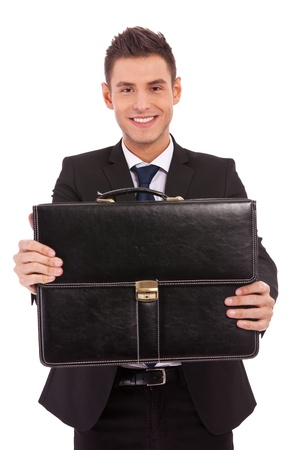 smiling young business man offering a black briefcase over white background Stock Photo - 13311014