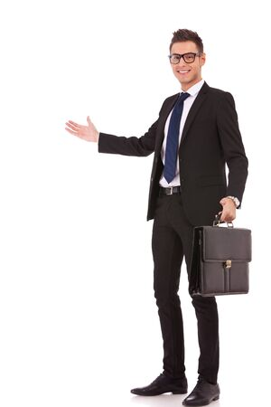 suit case: Smiling business man with a briefcase welcoming you on white background Stock Photo