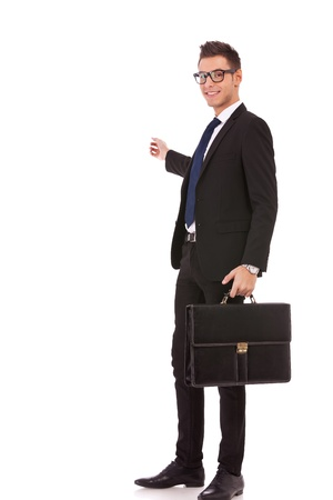suit case: Happy business man with briefcase presenting and showing with copy space for your text isolated on white background