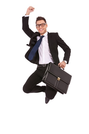 excite: Excited business man with briefcase jumping in mid-air cheering and celebrating his success  Stock Photo