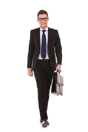 Ritratto di un uomo felice giovane, affari, una valigia, camminando su sfondo bianco