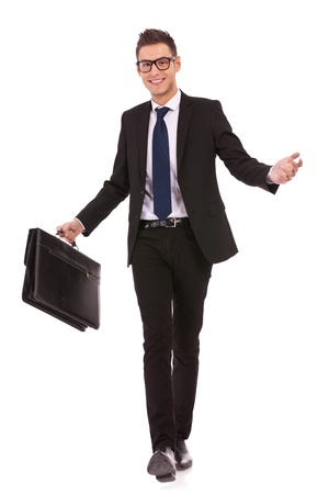 business case: young business man wearing glasses and holding a hand case, welcoming while walking, on white background