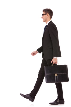 business man holding brief case and walking over white background Stock Photo - 13310564