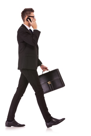 side view of a hurrying business man talking on the mobile phone on white background photo