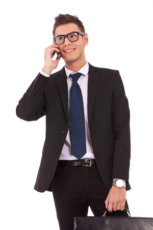 young business man speaking on the phone and looking away from the camera photo