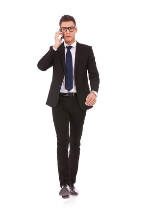 hücresel: Young business man with glasses talking on mobile phone while walking