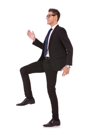 business man stepping up against a white background  photo