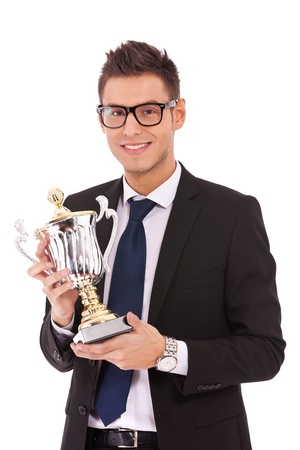 Happy business man holding a trophy over white background  photo
