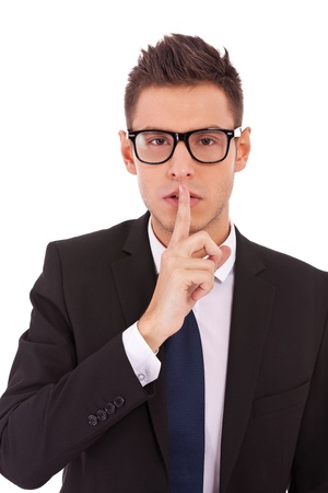 trade secret: young business man showing silence gesture on white background