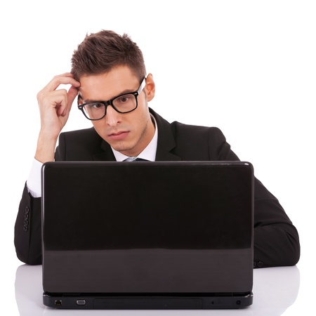 Serious executive with hand to head, looking at laptop on white