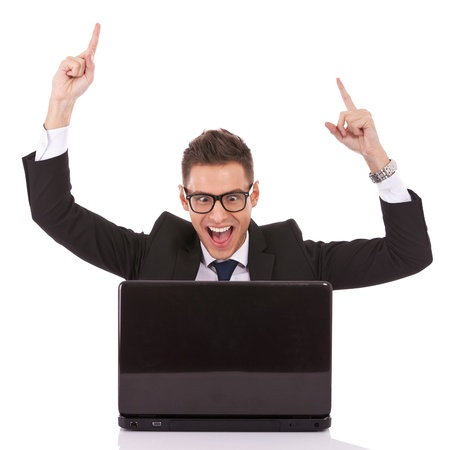 Happy arm rising winning business man at his desk working on laptop Stock Photo - 13310421