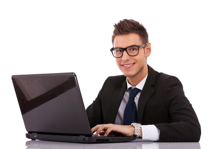 Smiling business man wearing glasses  using a laptop on white background Stock Photo - 13310817