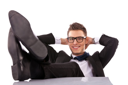 office shoes: Successful business man relaxing over his desk, isolated in white background  Stock Photo