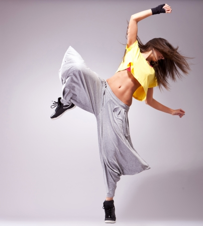 hip hop dancer: young woman dancer standing on one leg in a difficult dance pose