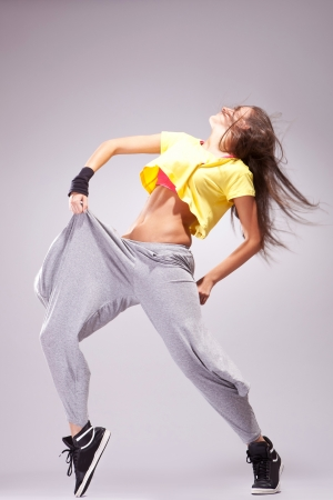 side view of a woman dancer in a full of energy dance pose photo
