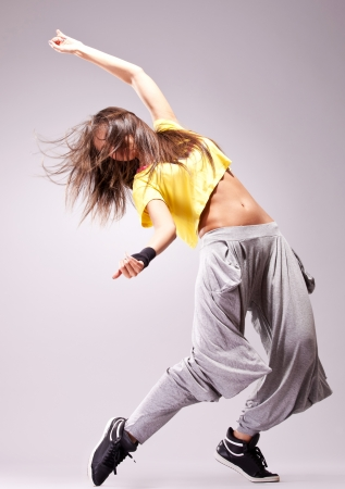 beautiful woman dancer in a passionate dance pose on gray background photo