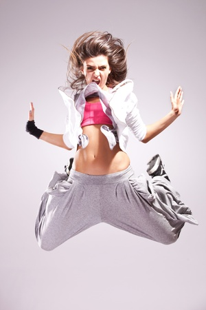 hip hop dance: Beautiful woman dancer screaming and jumping against gray background