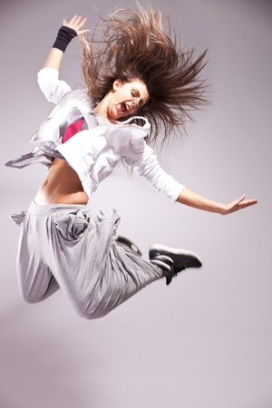 side pose: side view of a full of energy woman dancer screaming and making a difficult jump