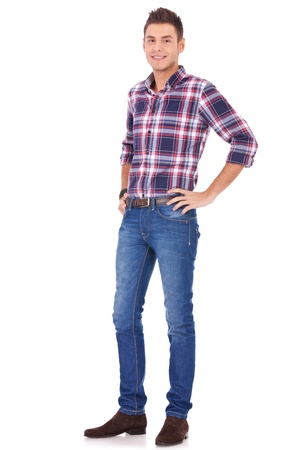 hand on hip: Young Man in Casual Clothes standing and smiling on white background