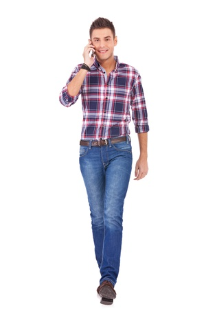 casual man walking towards the camera while talking on the phone on white background photo