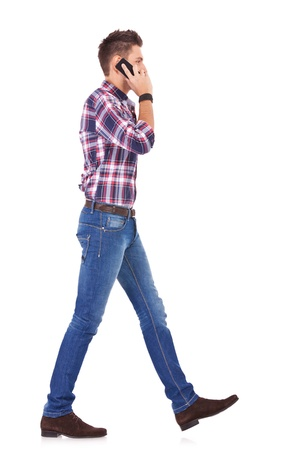 hurrying: side view of a casual man talking on the phone and walking on white background