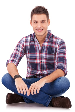 young youth: casual young man, smiling to the camera while sitting on white background  Stock Photo
