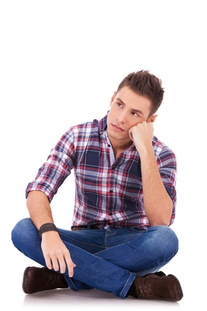 young casual man sitting on the floor, is looking a little sad to his side, on white background
