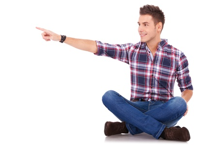 man side view: young casual happy man seated , pointing at something at his side, on white background